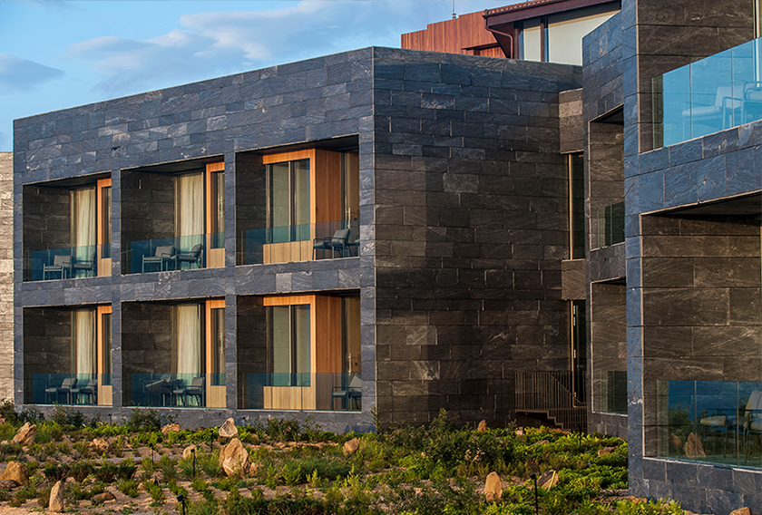 A ventilated facade clad in natural stone. Architects: mecanismo